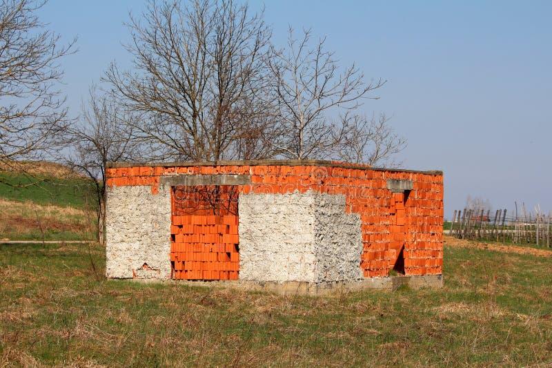 Construção exterior inacabado do tijolo vermelho sem telhado ou janelas cercado com grama sem cortes e árvores fotos de stock