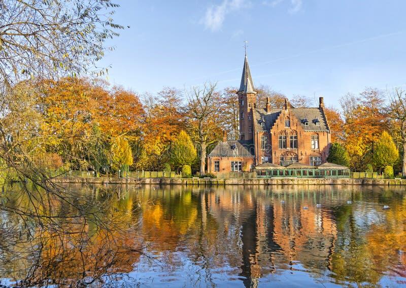 Construção flamenga do estilo que reflete no lago Minnewater, Bruges imagem de stock