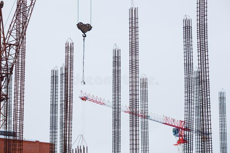 Construção, guindastes altos, estrutura do metal e reforço concreto imagem de stock