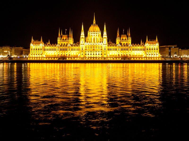 Construção histórica iluminada do parlamento húngaro na terraplenagem de Danube River em Budapest na noite imagem de stock royalty free