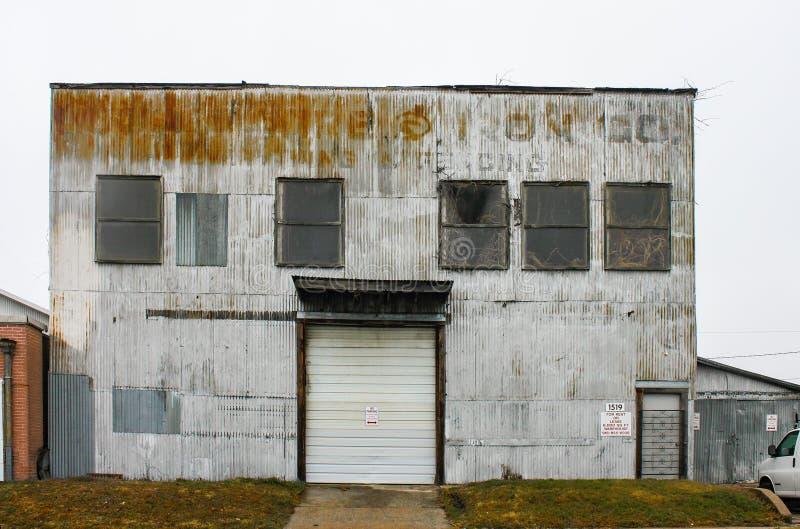 A construção industrial da chapa metálica velha com rotulação desvanecida e as plantas que crescem nas janelas e fora do telhado  fotos de stock royalty free