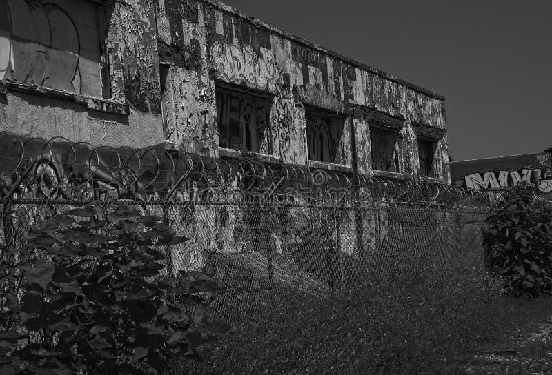 A construção industrial e o arame farpado abandonados bobinam preto e branco foto de stock