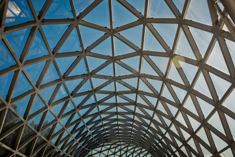 Construção moderna com encurvamento da coluna do aço do telhado e do vidro Fundo abstrato geométrico Gridded na perspectiva Const fotografia de stock