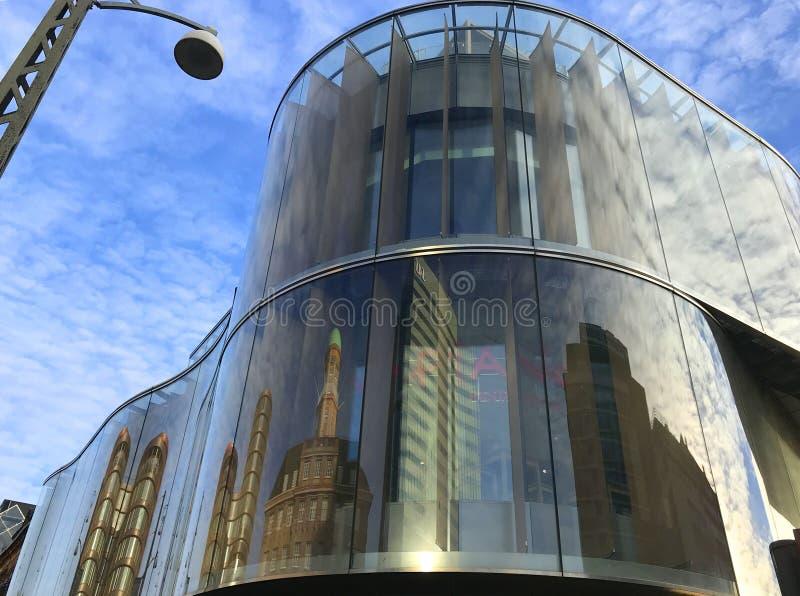 Construção moderna com parte dianteira de vidro arredondada contra um céu azul com nuvens brancas fotografia de stock