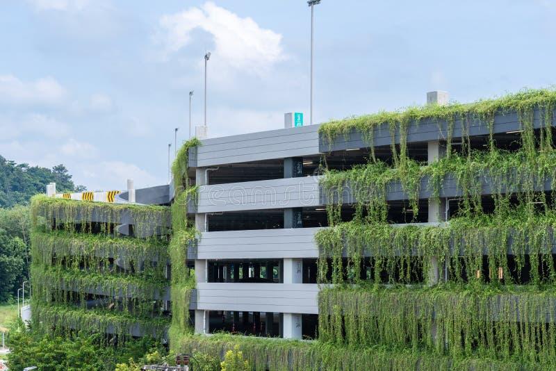 Construção moderna da garagem de estacionamento coberta com a planta, decoração exterior foto de stock