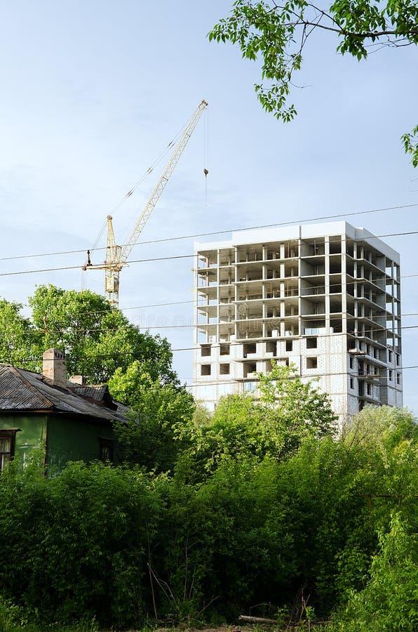 Construção nova na cidade e em uma casa velha no primeiro plano foto de stock royalty free