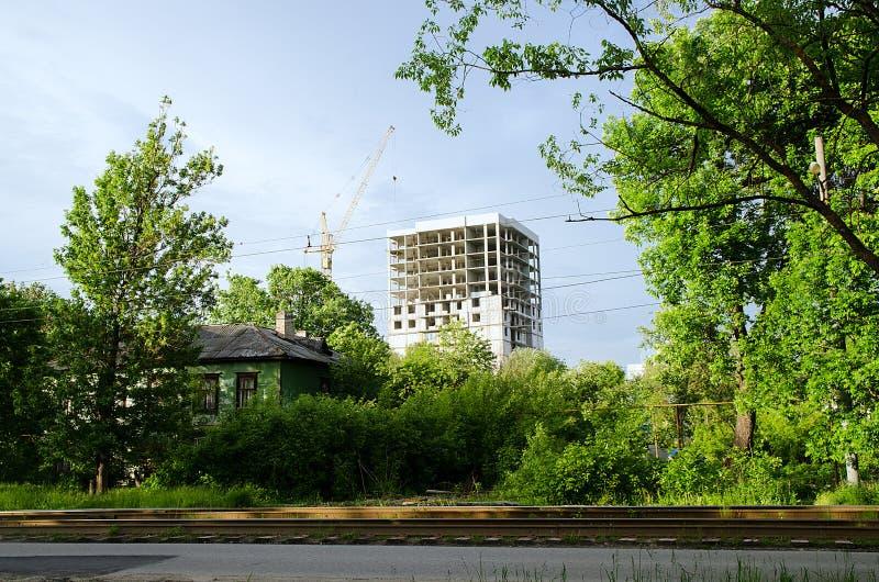 Construção nova na cidade e em uma casa velha no primeiro plano imagem de stock