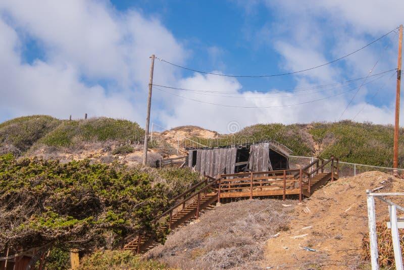 Construção pequena dilapidada no monte com a escadaria de madeira que conduz a ela Céu azul com nuvens inchado fotografia de stock