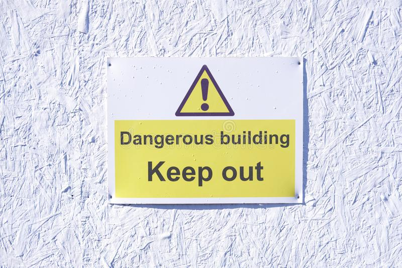 A construção perigosa mantém-se para fora advertir o sinal do cuidado na parede branca no terreno de construção da construção fotografia de stock royalty free