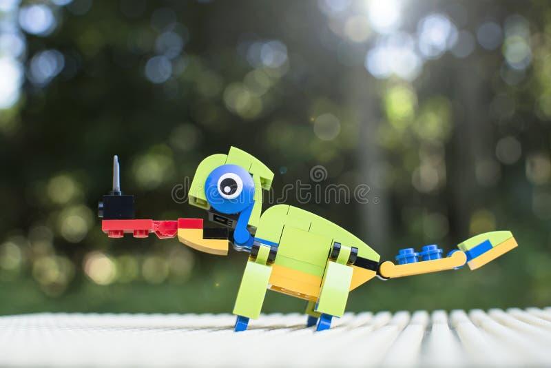 A construção plástica dos blocos cria um camaleão e o travamento do inseto pela língua com o fundo do jardim do bokeh foto de stock royalty free