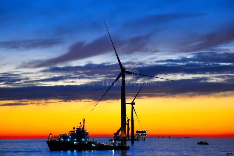 Construção a pouca distância do mar do windfarm no por do sol imagens de stock