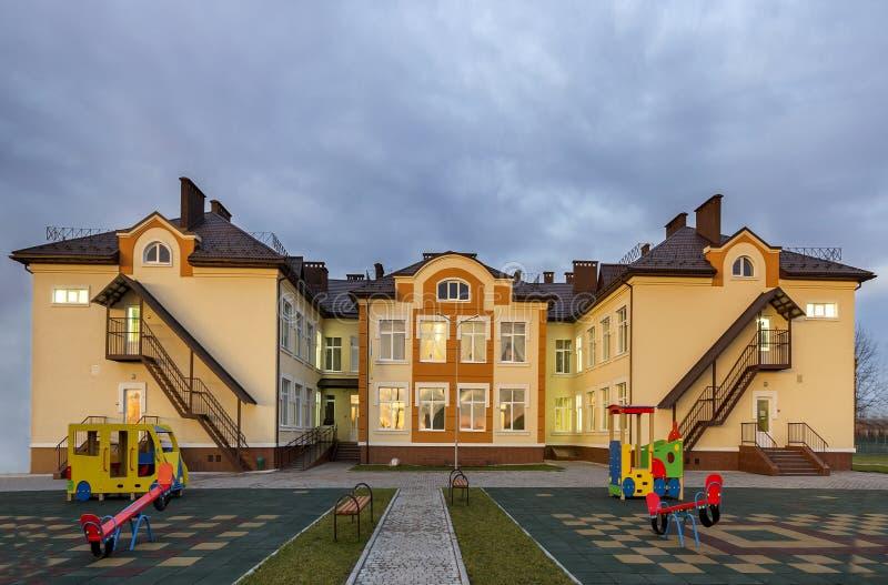 Construção pré-escolar do jardim de infância dois-contado moderno novo, balanços brilhantes do brinquedo no campo de jogos espaço imagem de stock