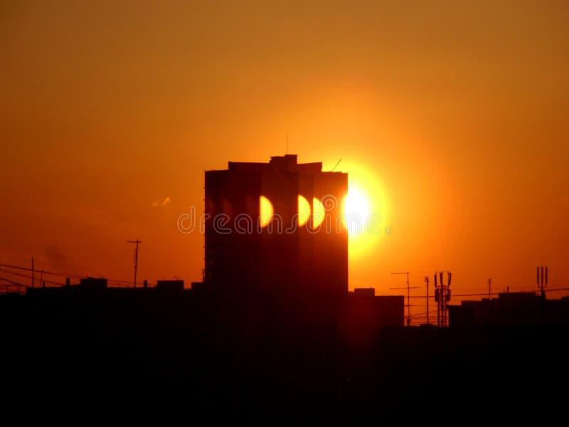 Construção preta contra um fundo do sol vermelho fotografia de stock royalty free