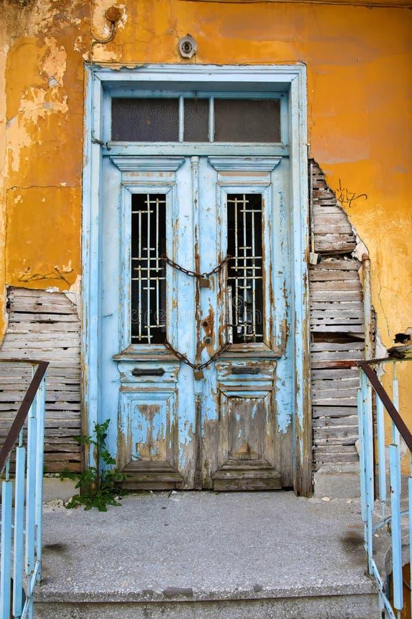 Construção velha abandonada com porta da rua acorrentada deteriorada imagem de stock royalty free