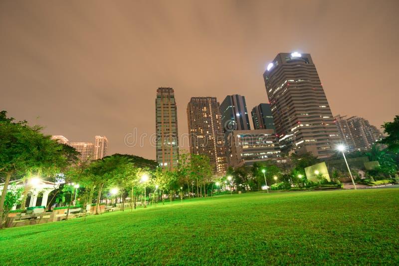Construções altas e parque público na noite em Banguecoque, Tailândia foto de stock royalty free