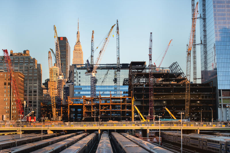 Construções altas sob a construção e guindastes sob um céu azul em New York imagem de stock