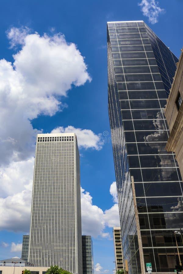 Construções da cidade moderna que projetam-se acima no céu nublado intensamente azul com reflexões imagens de stock