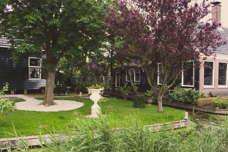 Construções de tijolo bonitas com jardim e gramado pelo rio Paisagem id?lico do campo Residência com o jardim perto do canal imagem de stock royalty free