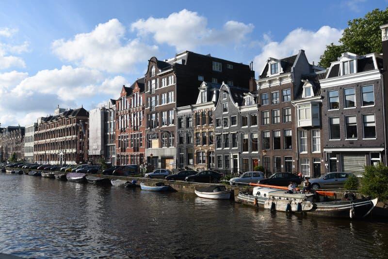Construções e barcos ao longo de um canal em Amsterdão fotos de stock