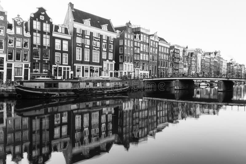 Construções e barcos ao longo dos canais de Amsterdão no preto e no Whit imagem de stock