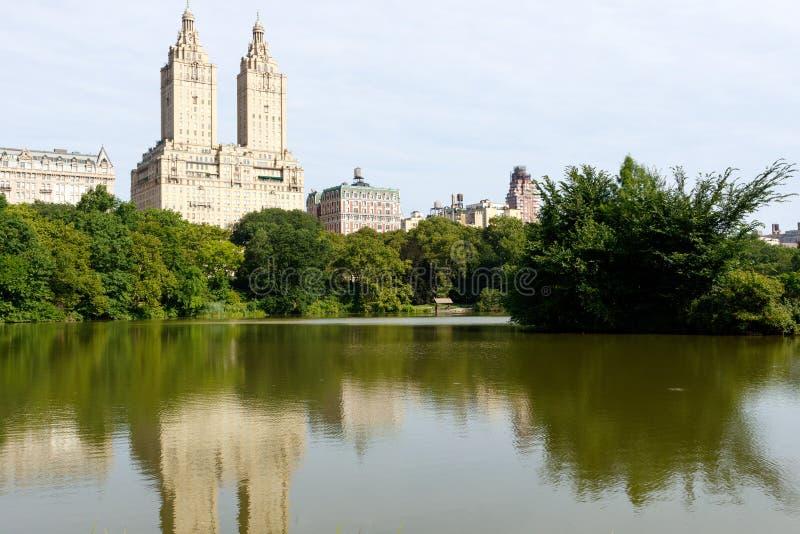 Construções e parque de New York City com lagoa fotografia de stock