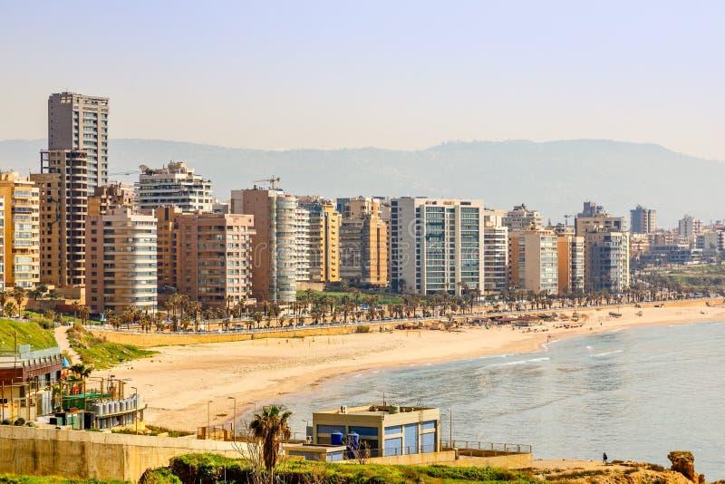 Construções e torres do centro com estrada, Sandy Beach e mar no primeiro plano, Beirute, Líbano fotografia de stock royalty free