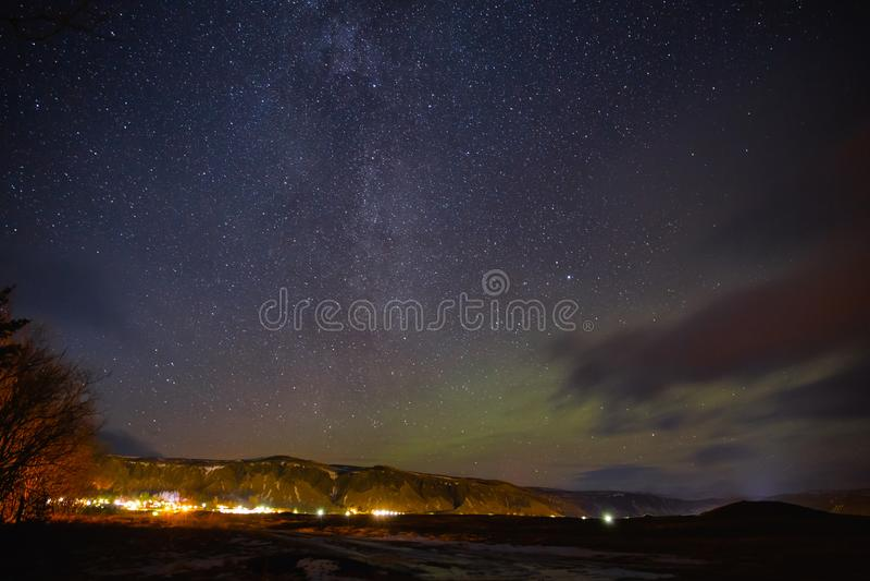 construções iluminadas e céu estrelado bonito com aurora boreal fotos de stock