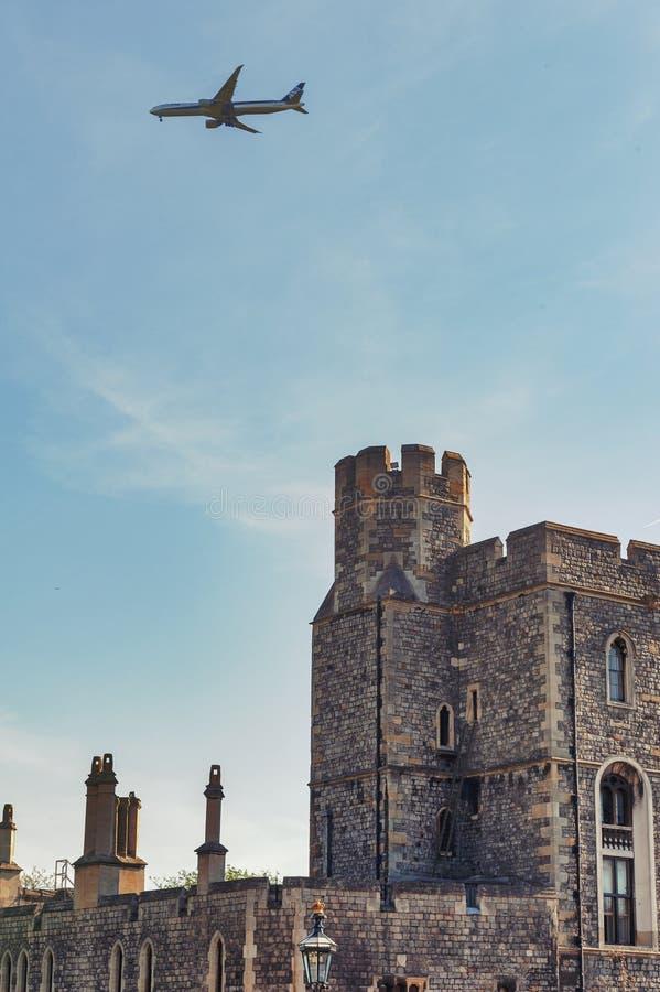 Construções na divisão mais baixa de Windsor Castle, uma residência real em Windsor em Berkshire, Inglaterra, com um avião que vo imagens de stock