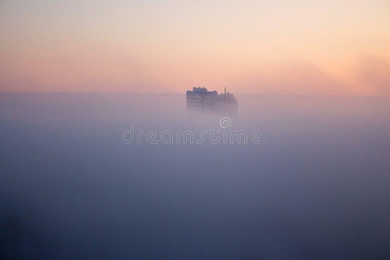 Construções no embaçamento da manhã Vista panorâmica da cidade enevoada Arquitectura da cidade nevoenta Nascer do sol e névoa sob imagem de stock royalty free