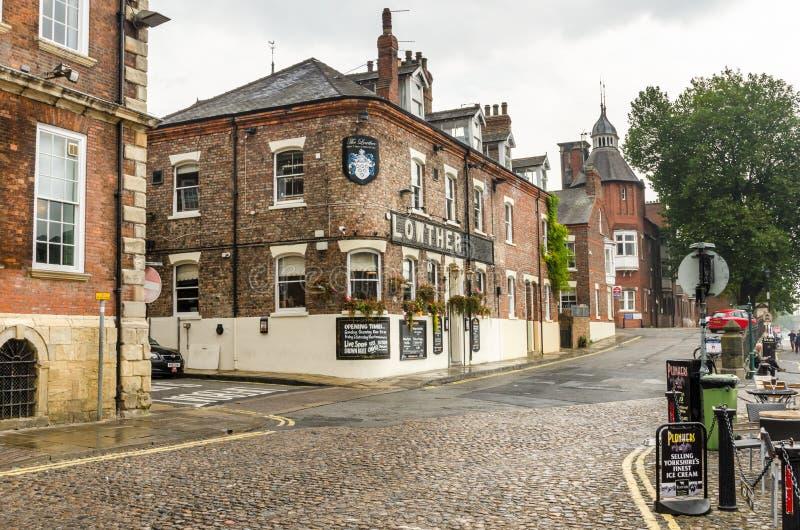 Construções tradicionais do bar e de tijolo no centro de cidade de York foto de stock