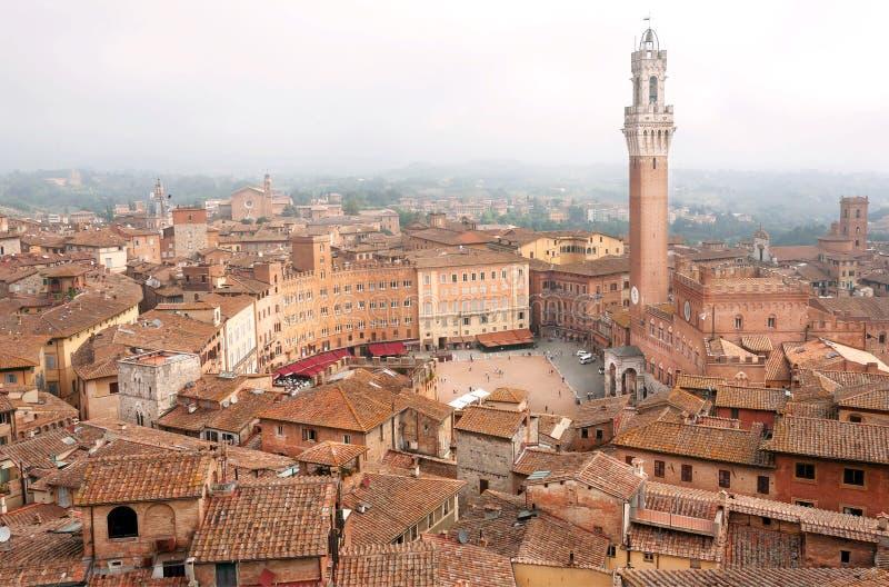 Construções velhas bonitas sob a névoa da manhã em Siena, Toscânia Telhados de telha e torre do século XIV Torre del Mangia, Itál imagens de stock