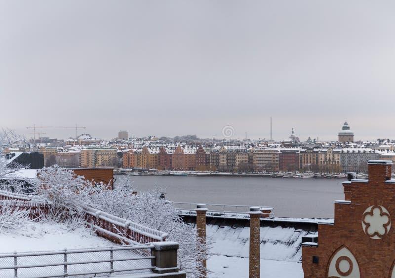 Construções velhas pelo rio em um dia de inverno úmido com neve e névoa, Suécia de Éstocolmo fotografia de stock