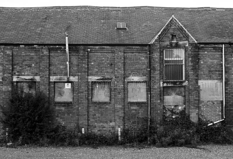Constru??o abandonada velha da f?brica do tijolo com as janelas ascendentes embarcadas e as paredes de deteriora??o de desintegra imagem de stock royalty free