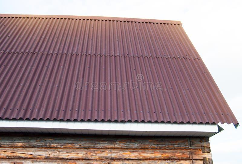 constru??o moderna do telhado com o metal vermelho que toma partido a uma casa de madeira no jardim fotografia de stock