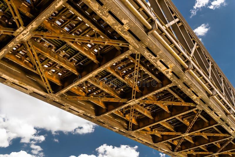 Construcción de acero del enrejado de un puente ferroviario en un fondo del cielo azul con las nubes blancas imágenes de archivo libres de regalías