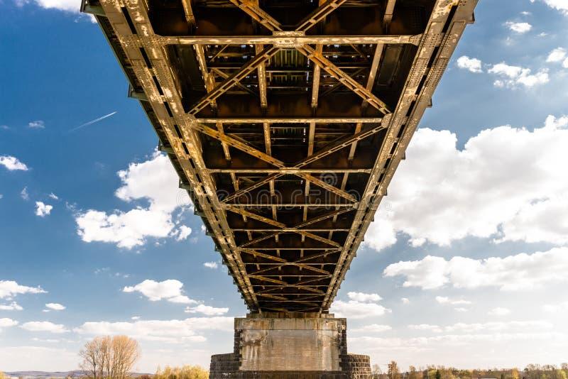 Construcción de acero del enrejado de un puente ferroviario en un fondo del cielo azul con las nubes blancas fotografía de archivo