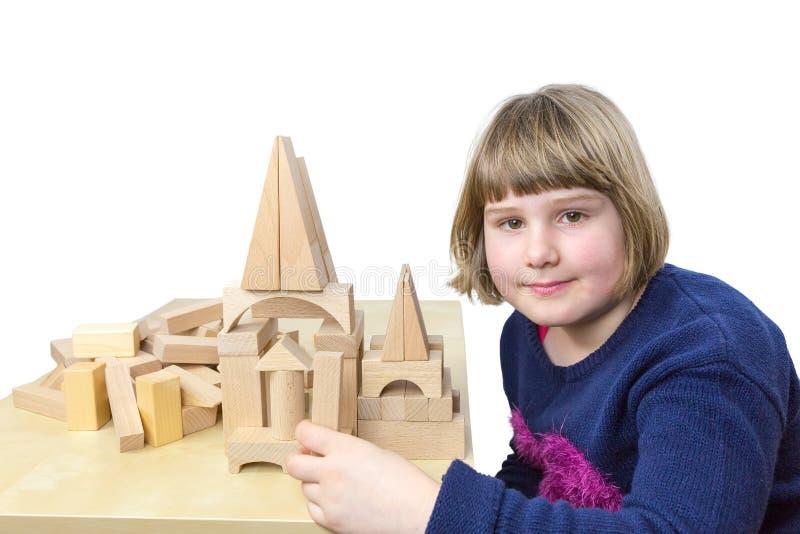 Construcción de edificios de la chica joven con los bloques de madera foto de archivo libre de regalías