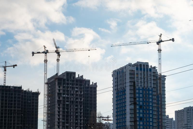 Construcción de edificios de varios pisos residenciales con la ayuda cuatro grúa fotos de archivo