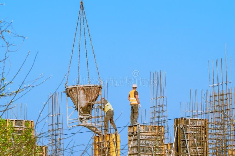 Construcción de la casa - los trabajadores concretos sirvieron la grúa imagen de archivo