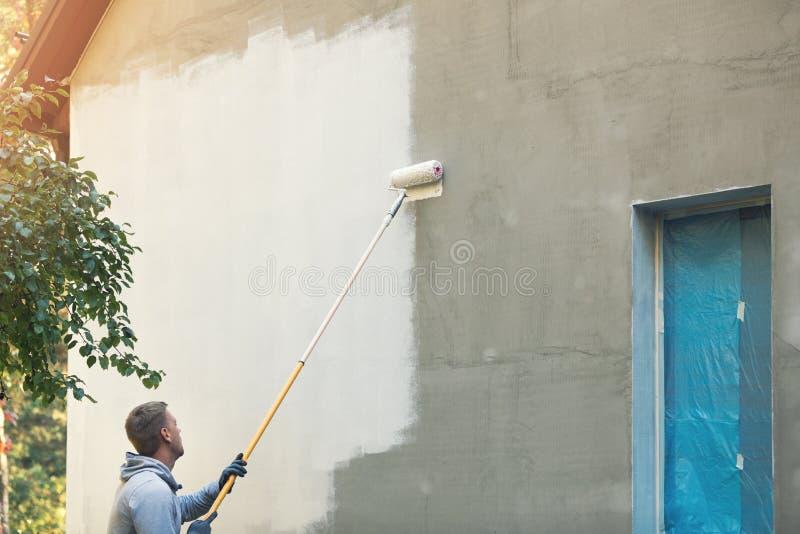 Construcción de la pintura del pintor de casas exterior con el rodillo fotos de archivo libres de regalías