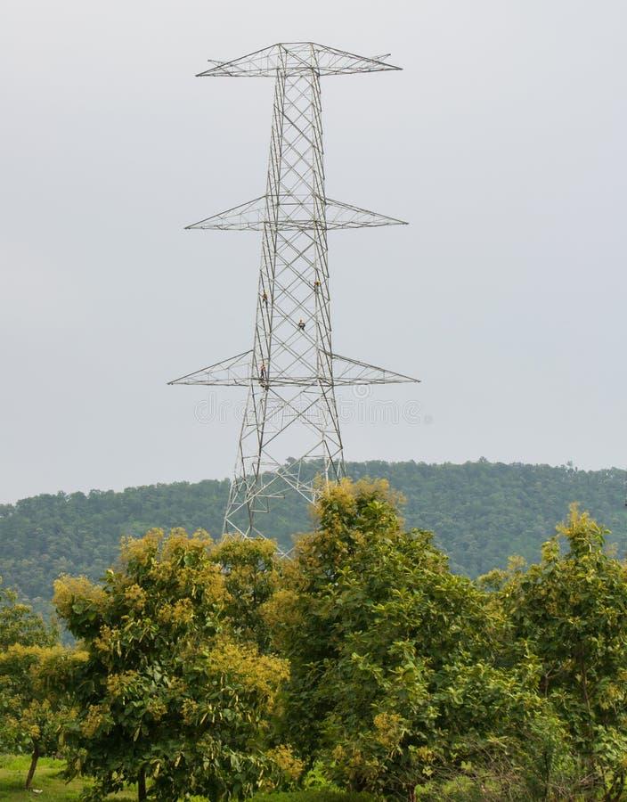 Construcción de la torre de la transmisión de la electricidad con los trabajadores imagenes de archivo