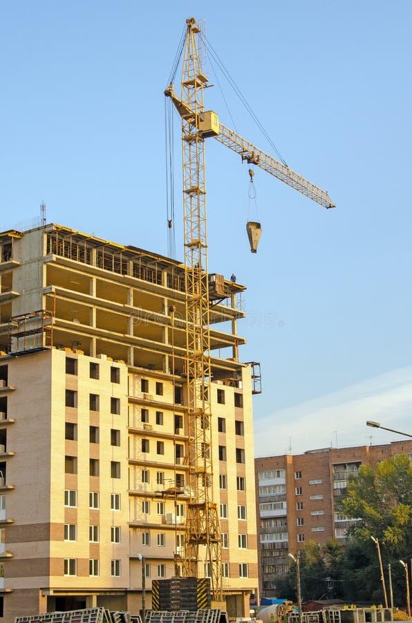 Construcción de un edificio de varios pisos Grúa en el trabajo Trabajadores en el último piso Ladrillo Rusia imagen de archivo libre de regalías