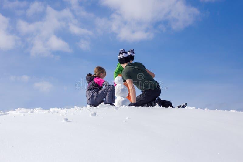 Construcción de un muñeco de nieve fotografía de archivo libre de regalías