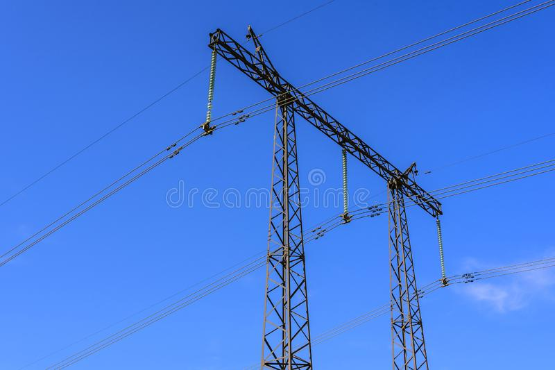 Construcción de una ayuda y de alambres de un primer de alto voltaje de la línea eléctrica contra un cielo azul imagen de archivo libre de regalías