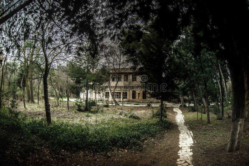 Construcción de viviendas abandonada del pueblo en el jardín de Baku Botanical Nadie en el parque con los árboles primavera foto de archivo