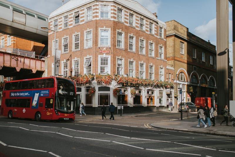 Construcción de viviendas clásica en el centro de ciudad de Londres, visto de la acera mientras que el autobús público rojo cruza foto de archivo