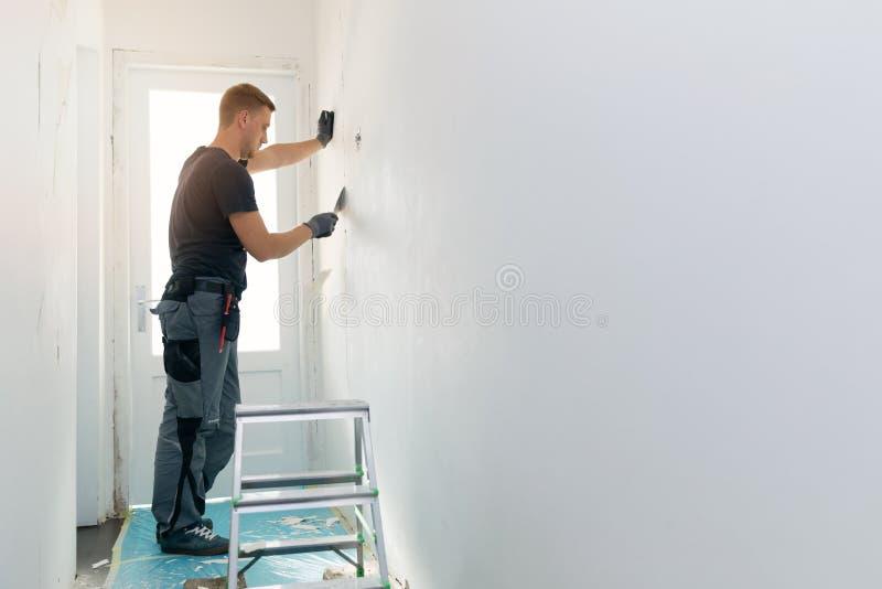 Construcción interior casera - trabajador que repara la pared fotos de archivo libres de regalías