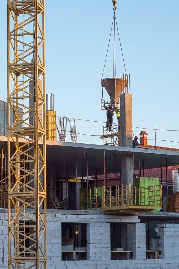 Construcción Los trabajadores concretos realizan el trabajo concreto imagenes de archivo