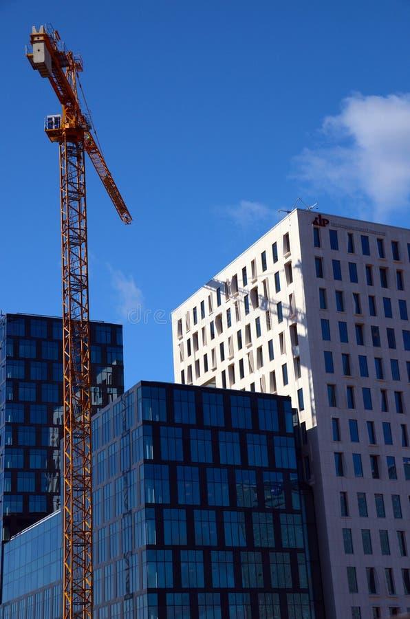 Construcción moderna de la arquitectura con luz del día fuerte y la grúa fotos de archivo