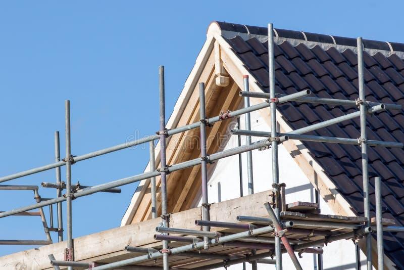Construcción moderna del tejado de la casa con la plataforma del polo del andamio fotos de archivo